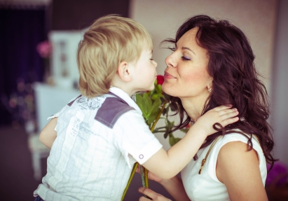 little cute boy and his mother kiss each other